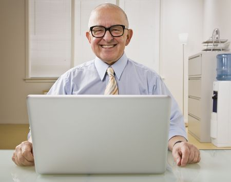 An elderly man is on a laptop in an office.  He is smiling at the camera.  Horizontally framed shot.