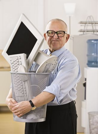 An elderly businessman is holding a trash bin with a computer screen in it.  He is looking at the camera.  Vertically framed shot.