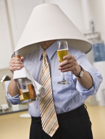 Male wearing lampshade on his head, holding Champagne bottle and glass in hands. Vertical
