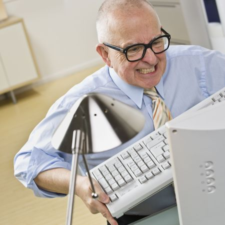 irate: An elderly businessman is working on a computer at an office, and appears to be angry at it.  Square framed shot.