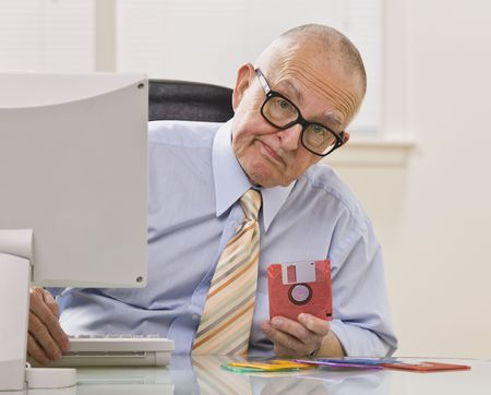 floppy disk: An elderly businessman is seated in an office holding a floppy disk.  He is looking at the camera.  Horizontally framed shot. Stock Photo