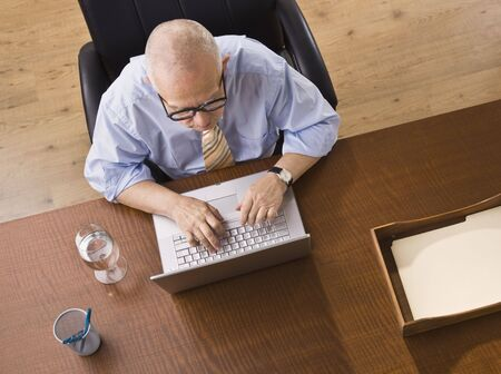 An elderly man is seated at a desk and is working on a laptop.  He is looking away from the camera.  Horizontally framed shot. photo