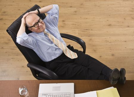 office desk: Attractive senior business man relaxing with feet on desk, reclining in chair, smiling at camera. Horizontal Stock Photo
