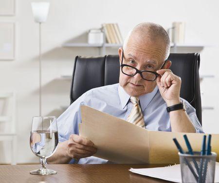 berisping: Een oudere man kijkt naar een bestand in een kantoor. Horizontaal framed shot. Stockfoto