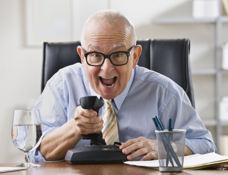 An elderly businessman is seated at a desk in his office and is joking around.  He is looking at a camera.  Horizontally framed shot. photo