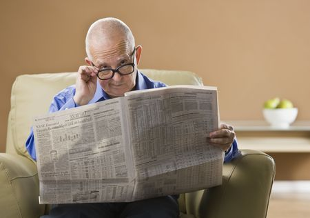 An elderly man is sitting in his living room reading a newspaper.  He is looking at the camera.  Horizontally framed shot.
