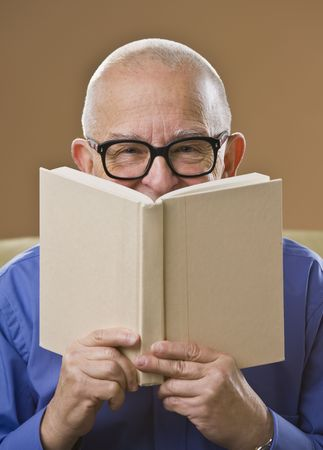 An elderly man is holding up a book and looking at the camera.  Vertically framed shot. photo