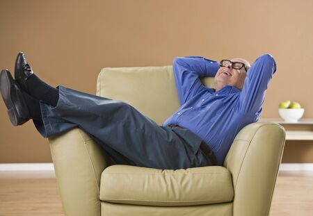 Attractive male senior laughing, while sitting on an overstufffed chair. Looking at the ceiling. Horizontal. Stock Photo
