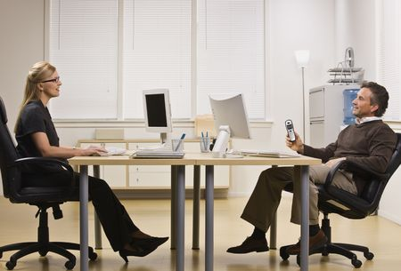 A businessman and woman are sitting across from each other at a desk in an office.  They are chatting with each other and looking away from the camera.  Horizontally framed shot. photo