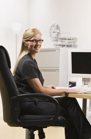 sitting down: A businesswoman is seated at a computer desk and smiling at the camera.  Vertically framed shot.