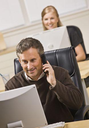 Een man en een vrouw werken op computers in een kantoor. De man praat over een telefoon. Ze zijn beide glimlachen op hun computer schermen. Verticaal framed shot.