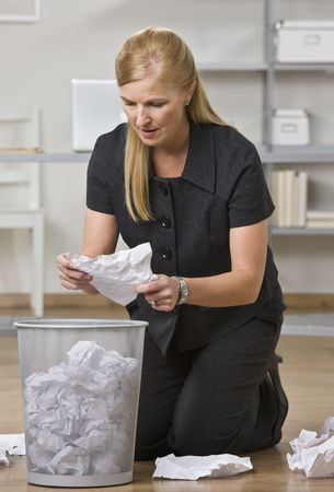 A businesswoman is on the floor in an office and is lookign through the trash.  She is looking away from the camera.  Vertically framed shot. Banco de Imagens