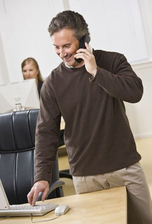 Attractive business man standing over keyboard while chatting on the phone. Woman peering in back. Looking at the computer screen. Vertical. Stock Photo - 5334016