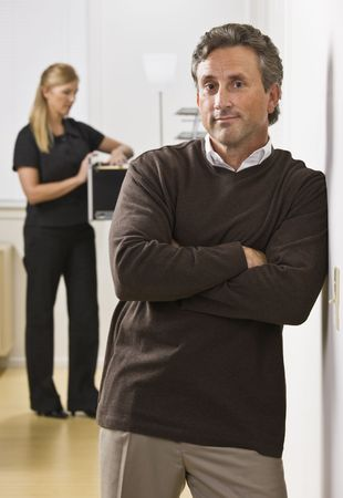 A businessman and woman are standing in an office.  The woman is looking in a filing cabinet and the man is looking at the camera.  Vertically framed shot. Stock Photo