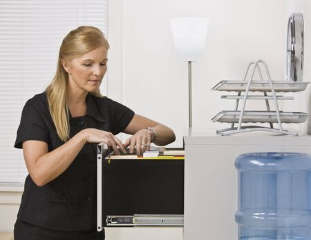 A businesswoman is in an office and is looking through a filing cabinet.  Horizontally framed shot.