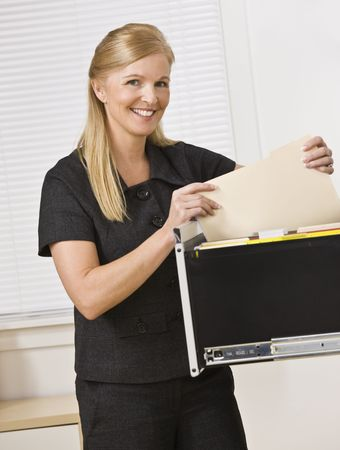 A businesswoman is looking through a filing cabinet and smiling at the camera.  Vertically framed shot.