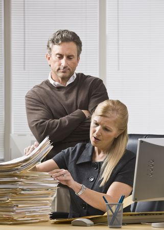 A businessman is standing in an office and looking over a woman's shoulder at the files on her desk.  She is looking away from the camera. Banque d'images