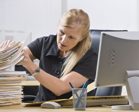 A businesswoman is seated at a desk in an office and is looking through a stack of paperwork.  Horizontally framed shot. photo