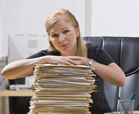 A businesswoman is seated at a desk with a large stack of paperwork in front of her.  She is looking at the camera.  Horizontally framed shot. photo