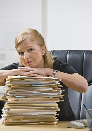 A businesswoman is seated at a desk in an office with a stack of paperwork.  She is looking at the camera.  Vertically framed shot. photo