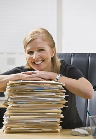 A businesswoman is seated at a desk in an office with a stack of paperwork.  She is smiling at the camera.  Vertically photo