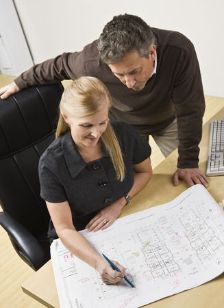 Two architects, male standing over female, looking at the drawing on the desk. Vertical photo
