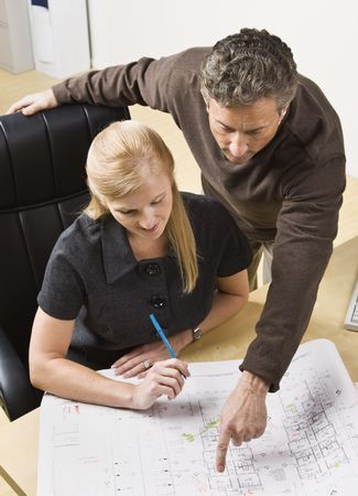 A man and a woman are working together on some blueprints in an office.  Vertically framed shot. photo