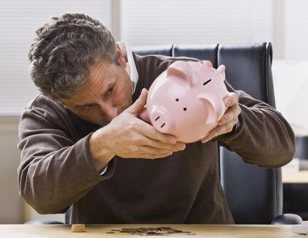 A businessman is seated at a desk in an office and is looking at a piggy bank.  Horizontally framed shot. photo