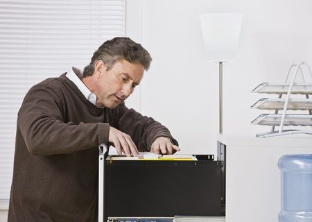 Attractive male wearing a sweater in office, looking for file in filing cabinet. Looking away from camera. Horizontal. Archivio Fotografico