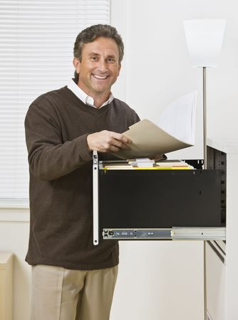 A businessman is standing in front of a filing cabinet and is smiling at the camera.  Vertically framed shot. photo