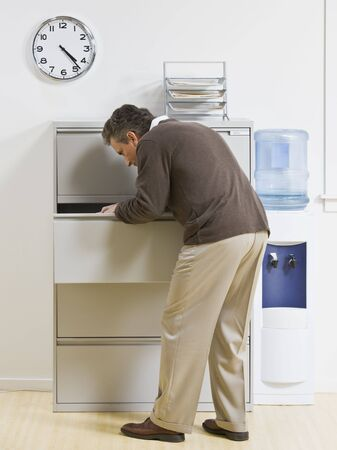 office cabinet: A businessman is looking through a drawer at an office.  Vertically framed shot.
