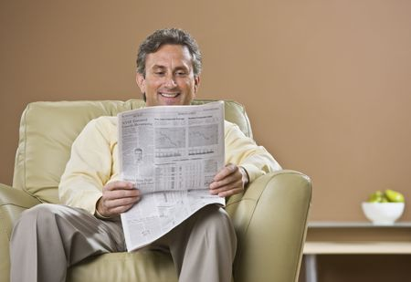 A man is reading a newspaper.  He is smiling and looking down at the paper.  Horizontally framed shot. photo