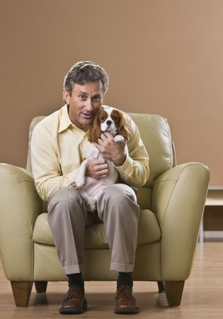 A man is seated in a chair in a room and is holding a puppy.  He is smiling at the camera.  Vertically framed shot. photo