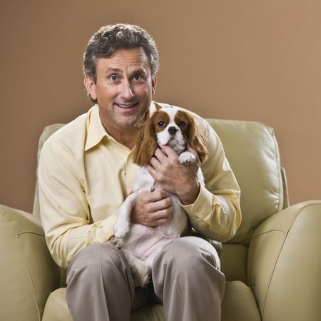 A man is seated in a chair holding a puppy.  He is smiling at the camera.  Square framed shot. photo