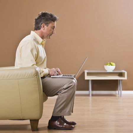 A businessman is seated on a couch and working on a laptop.  He is looking away from the camera.  Square framed shot. Stock Photo - 5333810