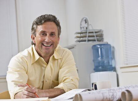 A businessman is seated at a desk in an office.  He is smiling at the camera.  Horizontally framed shot. photo
