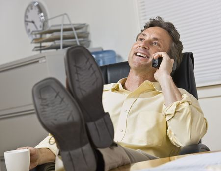 Attractive business man leaning back in chair, with legs on desk while chatting on the phone. Horizontal. photo