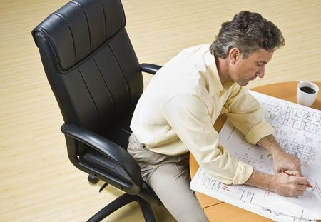 Attractive male siting at desk with drawings of home. Looking at desk. Horizontal Stock Photo - 5333503