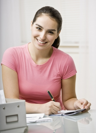 Young woman writing check to pay bills. Vertically framed shot.