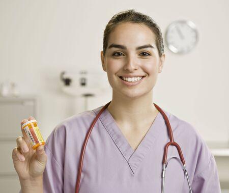 Young female medical professional holding medication. Horizontally framed shot. Stock Photo - 6393927