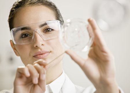 Young female scientist examining sample. Vertically framed shot. photo
