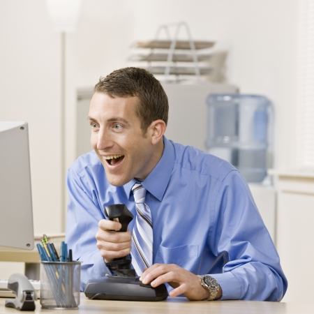 joystick: Young businessman playing video games at work. Square format.