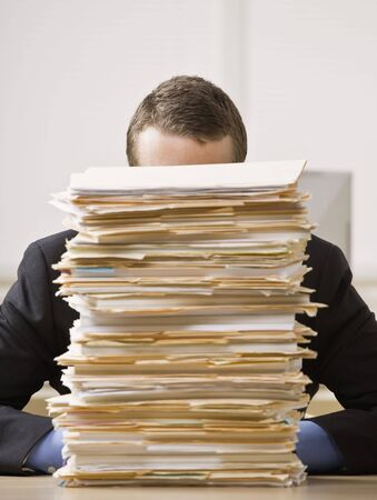files: Business man hiding behind tall stack of folders. Vertically framed shot.