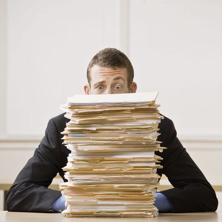 stack of files: Business man behind tall stack of folders. Square format. Stock Photo