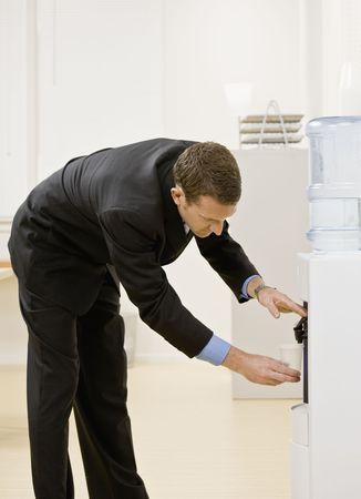 굽힘: Business man getting water from water cooler. Vertically framed shot.