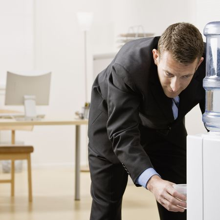 office space: Business man getting water from water cooler. Square format. Stock Photo