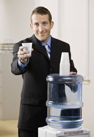 30s: Business man getting water from water cooler. Vertically framed shot.