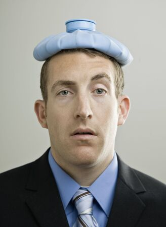 pained: Business man with ice pack on head. Vertically framed shot.