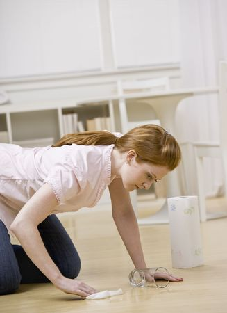 three persons only: Young woman cleaning up spill from floor. Vertically framed shot. Stock Photo