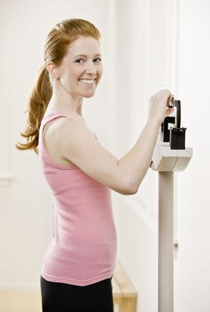 Young woman on scales after exercising. Horizontally framed shot. photo